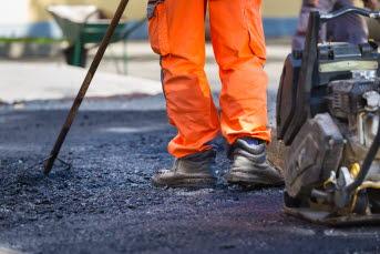Bild på en person som lägger asfalt.