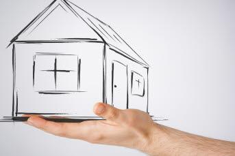 Bilden föreställer en hand som hållet i ett ritat hus