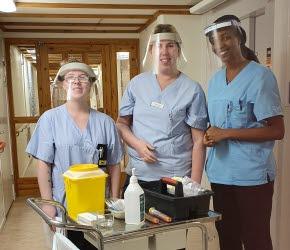 Syntolkning av bild: Tre kvinnor iklädda blåa arbetsskjortor och med visir över ansiktena. Framför står en vagn med olika redskap och tillbehör för att kunna utföra vaccinering.