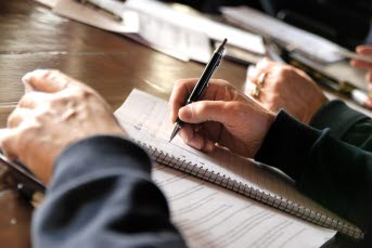 Bilden föreställer en hand som skriver i ett block.