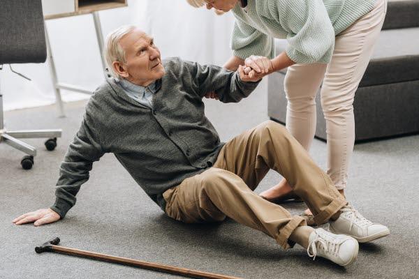 Bilden visar en äldre man som får hjälp att ta sig upp från golvet
