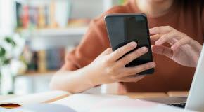 En yngre person sitter vid ett skrivbord och håller i en smartphone. På bordet står en bärbar dator.