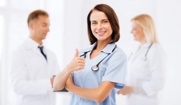 Bilden visar en vårdpersonal som gör tummen upp framför två andra vårdanställda