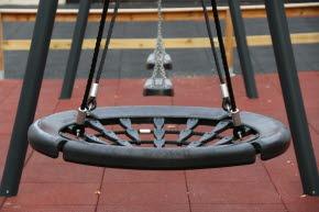 Närbild på en gungställning med tre stycken lågt hängande gungor.