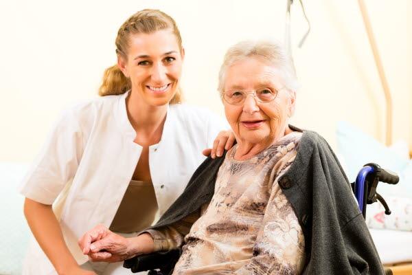 Bilden visar en ung kvinna i vårdarbetsklädsel med en äldre kvinna i rullstol