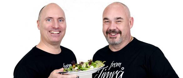 Bilden föreställer kommunchef och näringslivschef som håller i varsin tallrik mat.