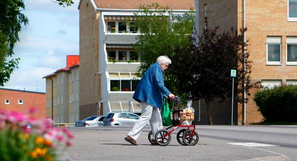 Bilden föreställer en äldre dam med rullator på promenad i Sörberge