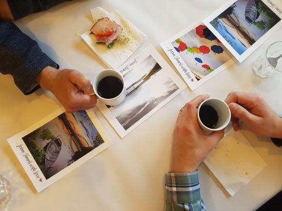 Händer som håller i kaffekoppar på ett bord.