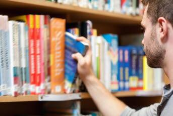 Bild på en person i ett bibliotek.