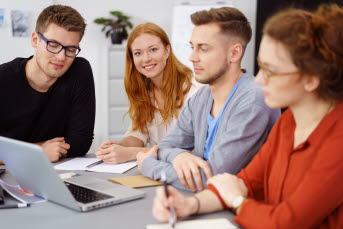 Bilden föreställer en grupp människor som sitter framför en dator