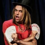 Bilden föreställer artisten Carl-Einar Häckner som har svart hatt och håller i kortlek i båda händerna
