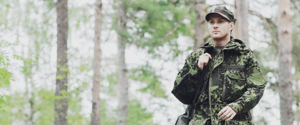Bilden föreställer en militärsoldat i skogen.