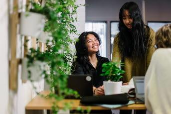 Tre kvinnliga studenter runt ett bord. Gröna växter hänger på väggen.