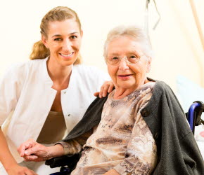Bilden visar en vårdpersonal med en äldre kvinna i rullstol