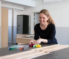 En kvinnlig lärare står i ett klassrum framför ett bord. Hon är glad. På bordet ligger undervisningsmaterial i form av byggbara klossar i olika färger.