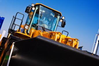 Bilden föreställer en traktor med traktorskopa.