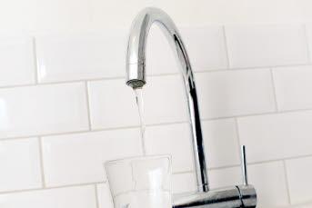 Bilden föreställer ett kökskran som häller vatten i ett glas