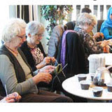 Bilden föreställer damer som stickar vid ett bord