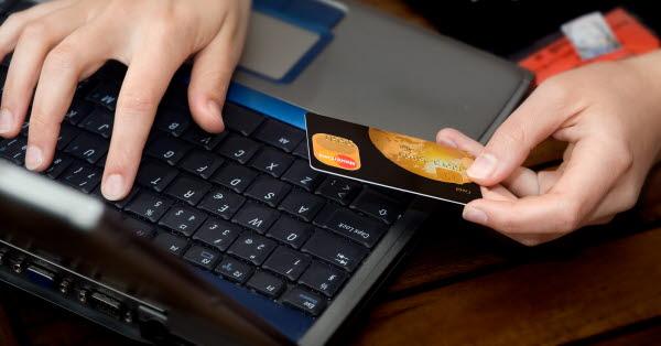 Bilden visar ett par händer med ett betalkort och ett tangentbord
