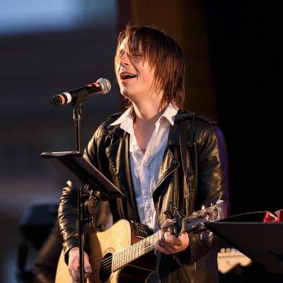 Bilden föreställer sångaren Klas Norberg som står och sjunger och spelar gitarr