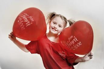 Bilden föreställer en flicka som håller två hjärtformade ballonger med texten from Timrå with love.