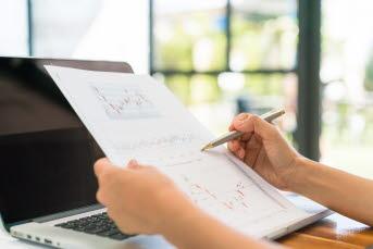 Bilden föreställer en människa som sitter vid en dator och antecknar på ett papper