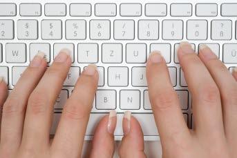 Bilden föreställer ett tangentbord med med händer.