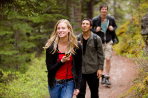 En kvinna med en GPS i handen promenerar i skogen. I sällskap bakom henne kommer två män gåendes.