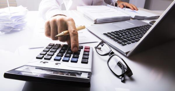 Bilden visar en hand med en miniräknare och tangentbord