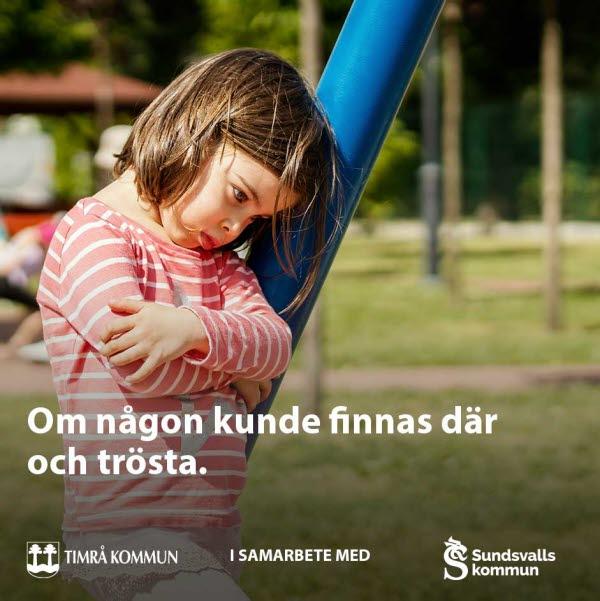 Ledsen flicka står ensam vid en ställning på en lekplats.