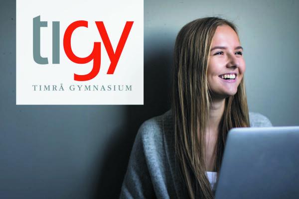 En tjej sitter ned mot en grå vägg, i knäet har hon en laptop. Hon har långt ljust hår, ett vitt linne och en grå stickad kofta. I övre vänstra hörnet ligger en vit platta med Timrå gymnasiums logotyp i grå och röd text.
