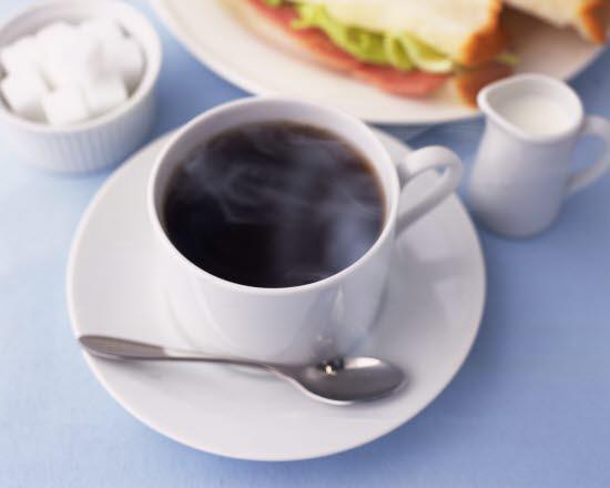 Kaffekopp med fat och sked. Sockerskål och gräddkanna.
