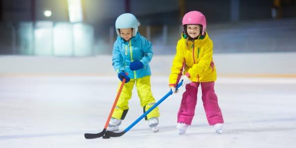 Bilden föreställer två barn på skridskor.