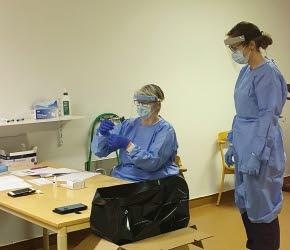En kvinna sitter vid ett bord och instruerar en annan kvinna i hur antigentestning fungerar. Båda kvinnorna är klädda i blåa arbetskläder och har blåa gummihandskar på händerna. Över ansiktet har de ansiktsmask och visir.