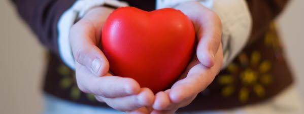 Bilden visar två händer som håller ett rött hjärta