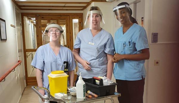 Tre kvinnor iklädda blåa arbetsskjortor och med visir över ansiktena. Framför står en vagn med olika redskap och tillbehör för att kunna utföra vaccinering.