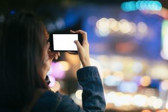 Bilden föreställer en person som tittar på mobiltelefonen.