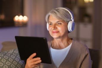 Kvinna sitter i soffa med hörlurar på huvudet och en mobiltelefon i händerna.