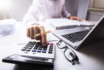 Bilden föreställer en hand som trycker på en miniräknare.