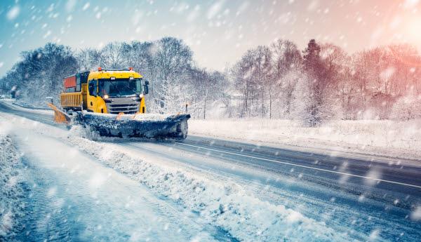 Snöplog plogar vägen i snöstorm.