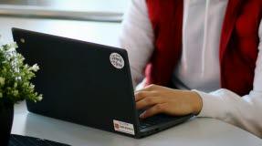 En elev i vit huvtröja och röd väst, sitter framför en svart Chromebook med händerna på tangenterna.