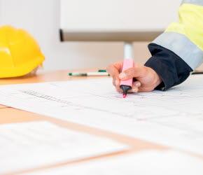 Bilden föreställer en bygglovhandläggare som studerar en ritning