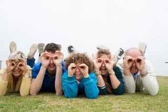 Bilden föreställer människor som ligger på marken och kikar genom sina händer.