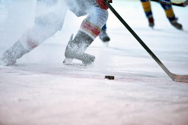 Bilden föreställer en person med skridskor, hockeyklubba och puck.