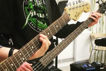 Bild på två elever som spelar gitarr.