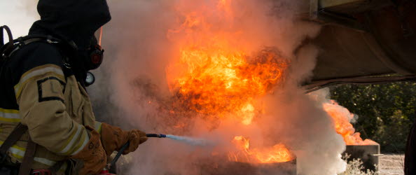 En elev med skyddskläder och brandsläckare, släcker en flammande eld.
