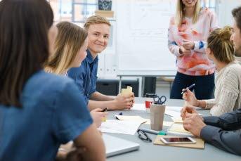 Bilden föreställer en grupp med människor och en ung kille tittar in i kameran.