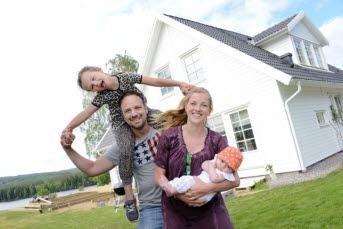 Bilden föreställer en familj med ett nybyggt hus.