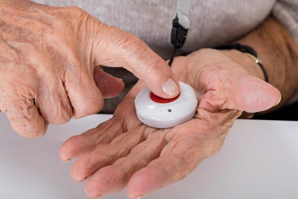 Bilden visar ett par händer som trycker på en larmknapp