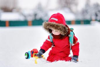 Bild på ett barn som leker i snön.